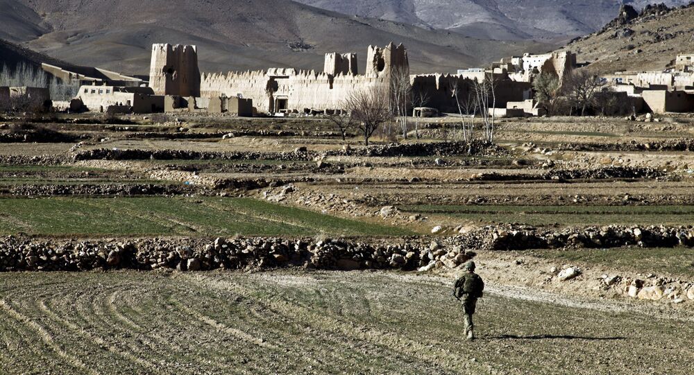 A US Army Soldier 1st Platoon, Apache Company, 2nd Battalion, 4th Infantry Brigade Combat Team, 10th Mountain Division, walks through a field to the village of Dahanah, Wardak province, Afghanistan Dec. 2.