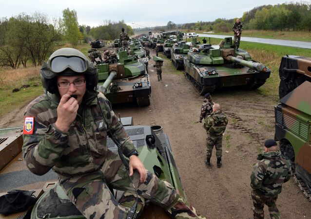 French soldiers unload tanks from a train in Drawsko Pomorskie, northern Poland on April 28, 2015. Fifteen French tanks and 270 soldiers come to Drawsko Pomorskie for a seven-week-long execise