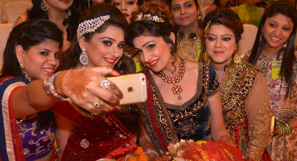 India women take a photograph with their mobile phone during celebrations of the Karva Chauth (Husband's Day) festival in Amritsar on October 30, 2015
