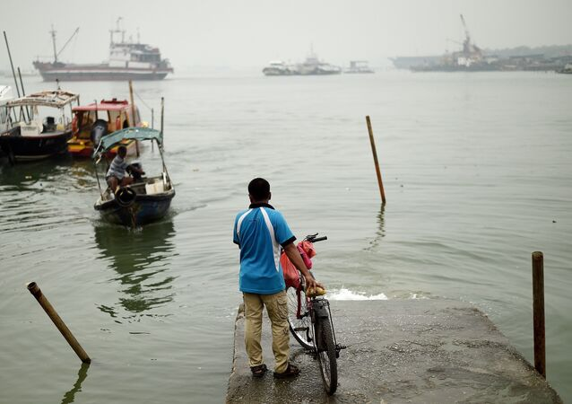 A local resident waits for a boat to cross the island during a thick blanket of haze over Port Klang on October 20, 2015