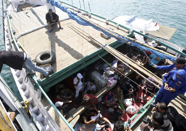 In this May 12, 2013 file photo, Iranian asylum seekers who were caught in Indonesian waters while sailing to Australia, sit on a boat, at Benoa port in Bali, Indonesia