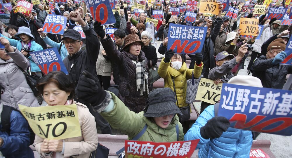 Anti-U.S. base protesters hold placards with a slogan that reads: No to Henoko new base during a rally in Tokyo, Sunday, Nov. 29, 2015