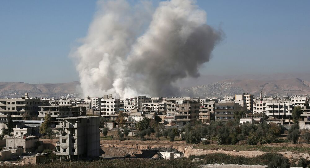 Smoke billows from buildings following a reported air strike in Damascus' rebel-held suburb of Zamalka on December 6, 2015