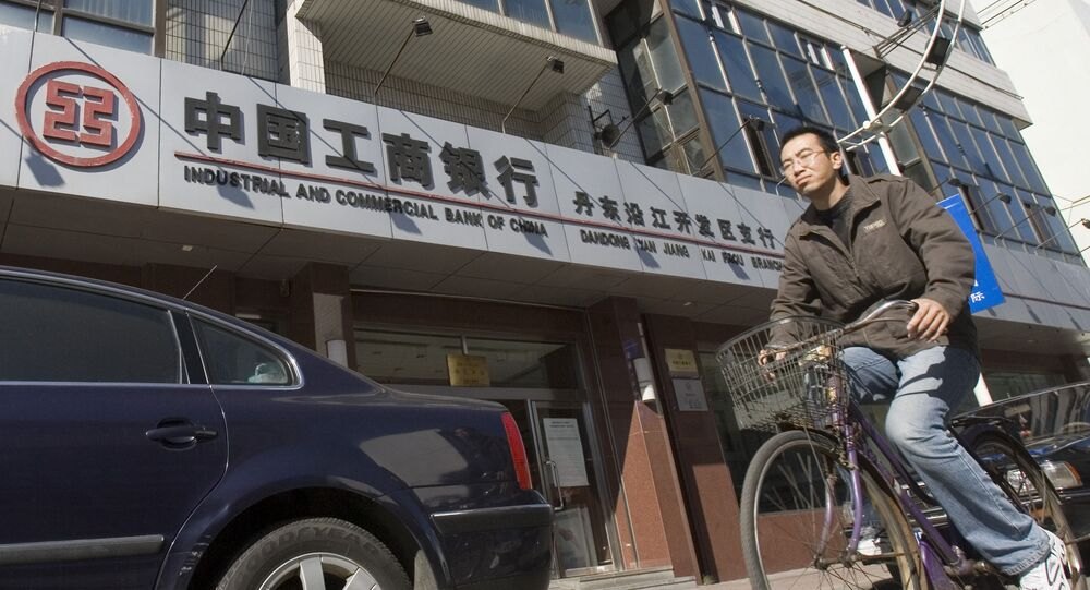 A man rides past a branch of the Industrial and Commercial Bank of China in the border city of Dandong in northeast China