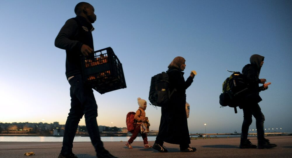 Refugees and migrants walk after disembarking from passenger ferry Blue Star1 at the port of Piraeus, near Athens, Greece, February 20, 2016.