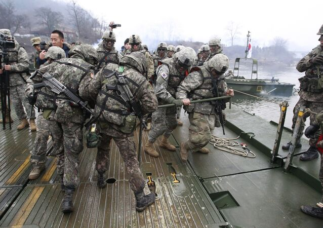 U.S. and South Korean, left, army soldiers work together to set up a floating bridge on the Hantan river during a river crossing operation, part of an annual joint military exercise between South Korea and the United States