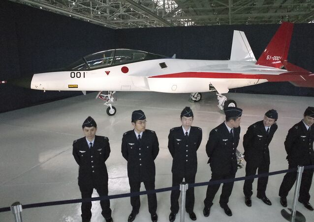 Defense Ministry officers stand in front of the first domestically-made stealth aircraft, X-2, at Nagoya Airport in Toyoyama town, central Japan, Thursday, Jan. 28, 2016.