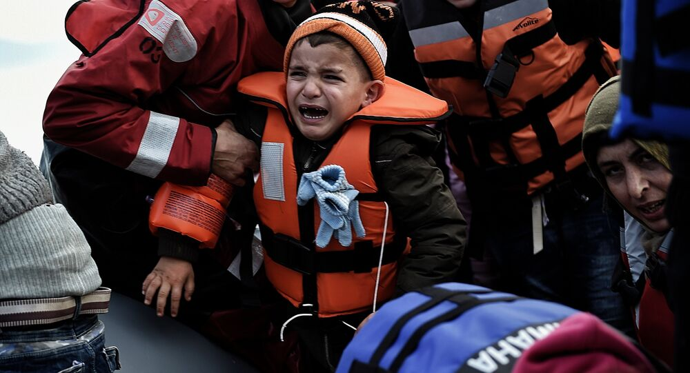A child reacts as refugees and migrants disembark a rubber boat upon arrival at the northern island of Lesbos after crossing the Aegean sea from Turkey, in Mytilene, on February 23, 2016.