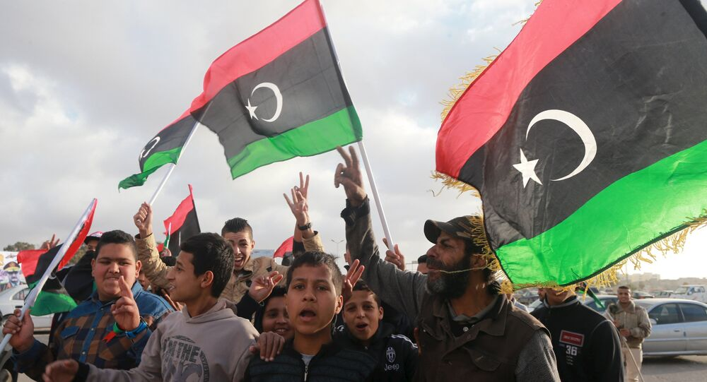 Libyans wave their national flags as they celebrate Libya's eastern government's gains in the area, in Benghazi, Libya, February 24, 2016.