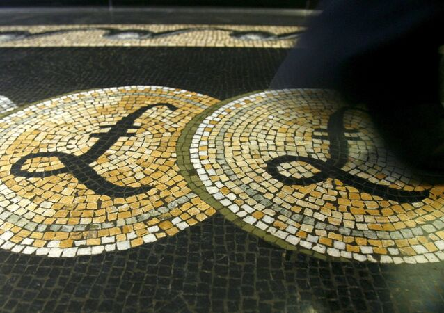 An employee is seen walking over a mosaic of pound sterling symbols set in the floor of the front hall of the Bank of England in London, in this March 25, 2008 file photograph.