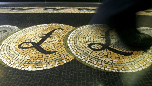 An employee is seen walking over a mosaic of pound sterling symbols set in the floor of the front hall of the Bank of England in London, in this March 25, 2008 file photograph.  - Sputnik International