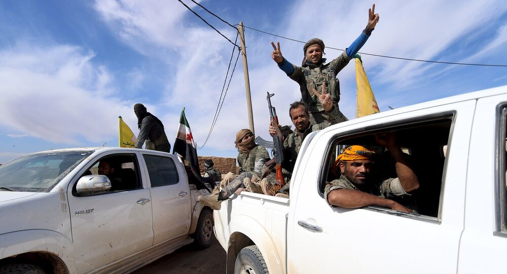 Syria Democratic Forces and Free Syrian Army fighters gesture on the back of pick-up trucks in a village on the outskirts of al-Shadadi town, Hasaka countryside, Syria
