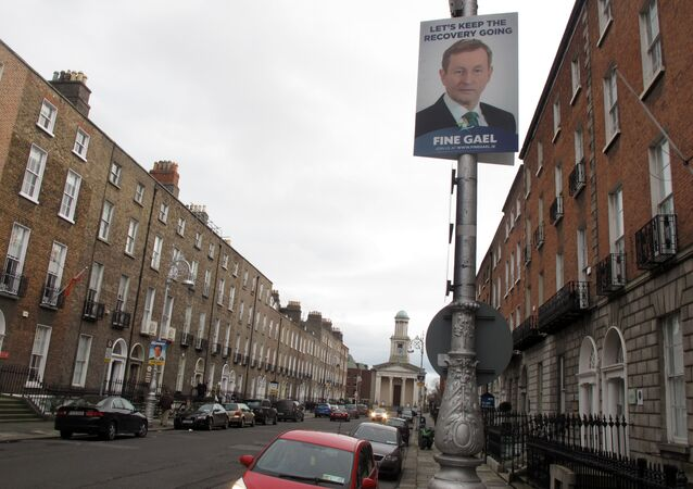 This photo taken Friday, Feb. 5, 2016, shows an election poster picturing Prime Minister Enda Kenny adorning a lamp post outside the headquarters of his Fine Gael party in Dublin, Ireland