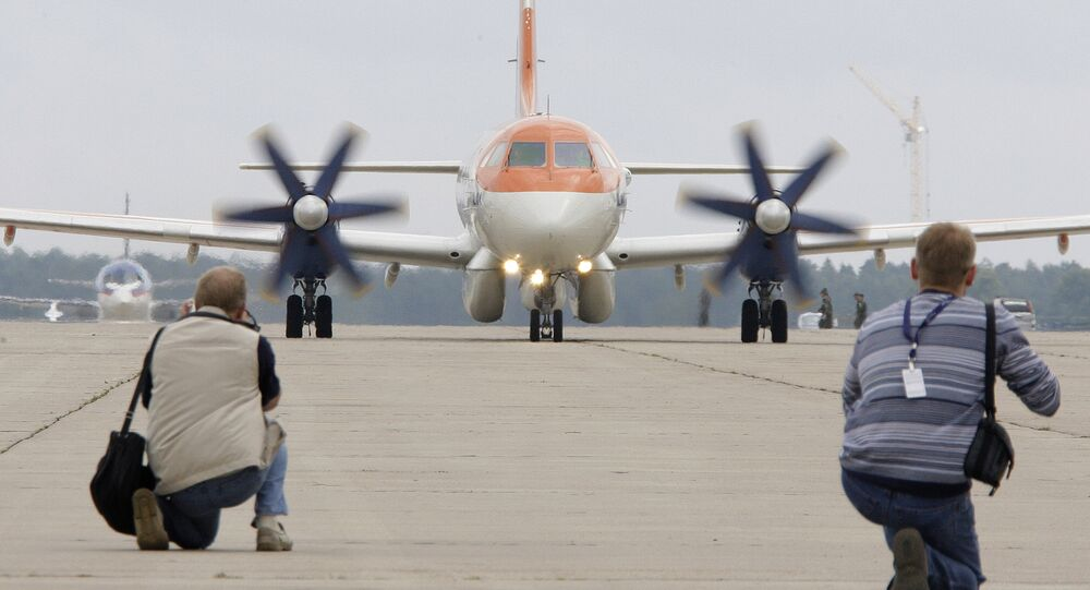 News photographers take pictures of an Ilyushin Il-114 passenger aircraft preparing to take off for a practice flight before the MAKS-2009 international aerospace show at the Zhukovsky Airfield