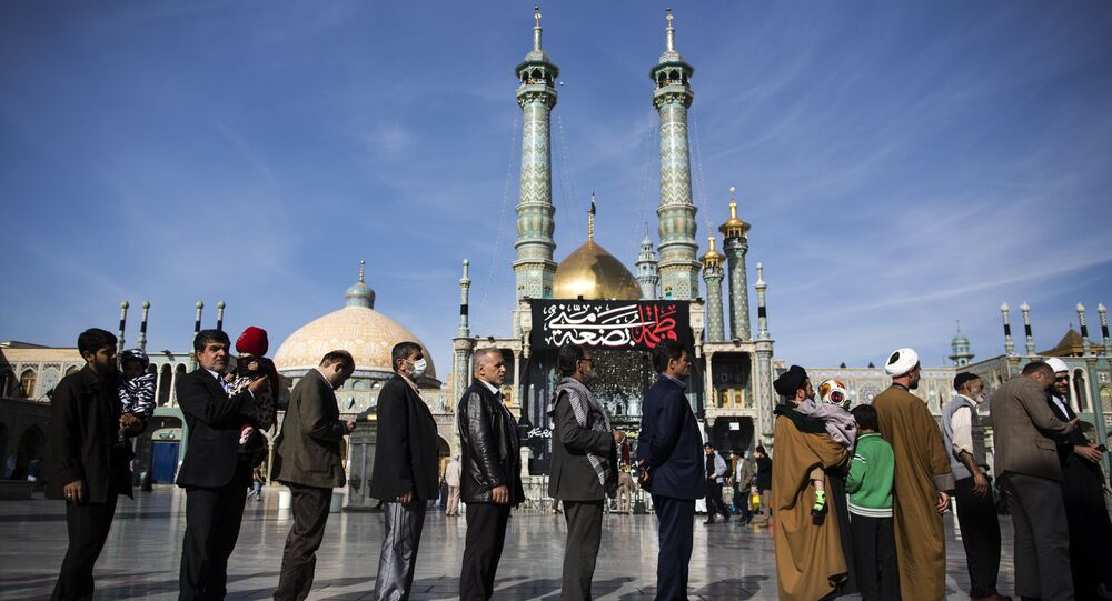 Iranians hold their identification cards as they line up outside a polling station at Massoumeh shrine during the parliamentary and Assembly of Experts elections at a polling station in the holy city of Qom, 130kms south of the capital Tehran, on February 26, 2016