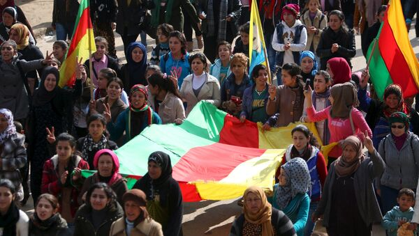 Kurdish people carry flags as they march during a protest in the city of al-Derbasiyah, on the Syrian-Turkish border, against what the protesters said were the operations launched in Turkey by government security forces against the Kurds, February 9, 2016 - Sputnik International