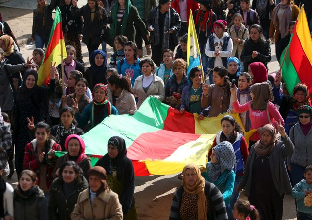 Kurdish people carry flags as they march during a protest in the city of al-Derbasiyah, on the Syrian-Turkish border, against what the protesters said were the operations launched in Turkey by government security forces against the Kurds, February 9, 2016