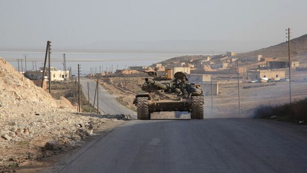 Syrian government forces drive a tank on a road during a military operation against Daesh in the villages of Zarour and Khanaser, in the Aleppo province, on February 26, 2016 - Sputnik International