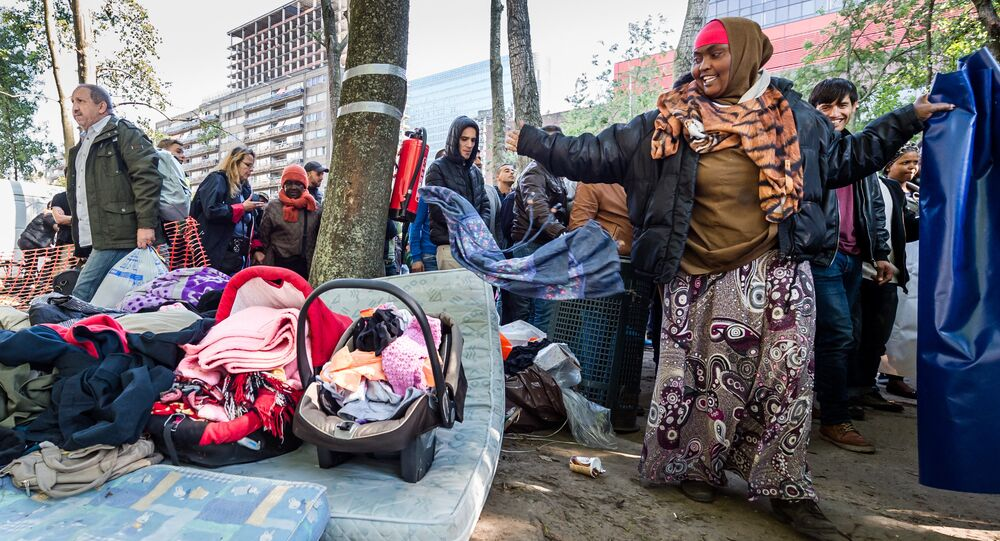 Refugees leave a tent camp for refugees in Brussels on Thursday, Oct. 1, 2015