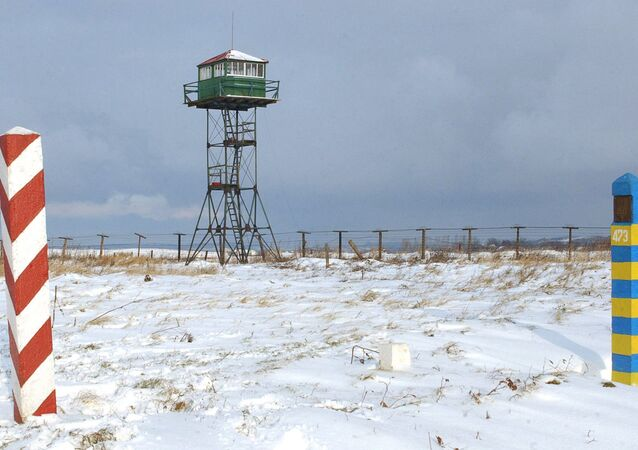 The remains of the old Soviet border barbed wire fencing and watchtower, used by Ukrainian border guards, are seen on the Polish-Ukrainian border, with Polish, left and Ukrainian border signs, in Sierakosce, southeast Poland, Friday, Dec. 14, 2007