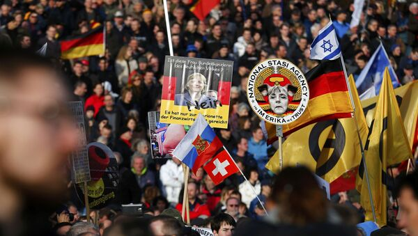 Supporters of the anti-Islam movement Patriotic Europeans Against the Islamisation of the West (PEGIDA) hold posters depicting German Chancellor Angela Merkel during a demonstration in Dresden, Germany, February 6, 2016 - Sputnik International