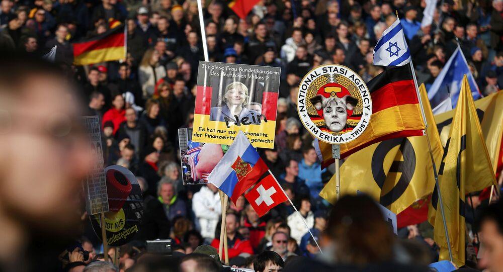 Supporters of the anti-Islam movement Patriotic Europeans Against the Islamisation of the West (PEGIDA) hold posters depicting German Chancellor Angela Merkel during a demonstration in Dresden, Germany, February 6, 2016
