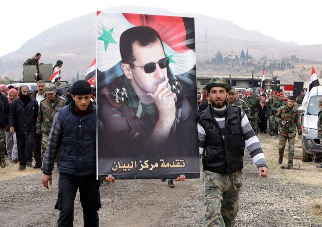 Syrian volunteers and their relatives wave the national flag and portraits of President Bashar Assad. File photo