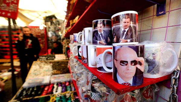 A Syrian vendor sells mugs bearing portraits of Russian President Vladimir Putin (bottom) and Syrian President Bashar Assad (top) in the popular Hamidiyeh market in the old part of the capital Damascus on November 26, 2015 - Sputnik International