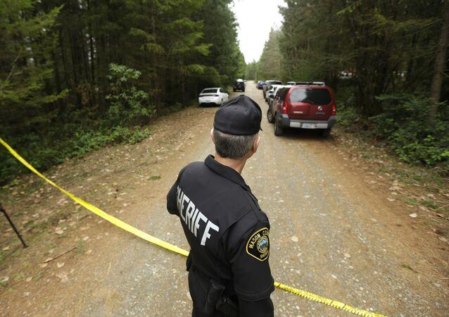 Mason County Sheriff's Chief Criminal Deputy Russ Osterhout looks down a road near the scene of a fatal shooting Friday, Feb. 26, 2016, near Belfair, Wash.