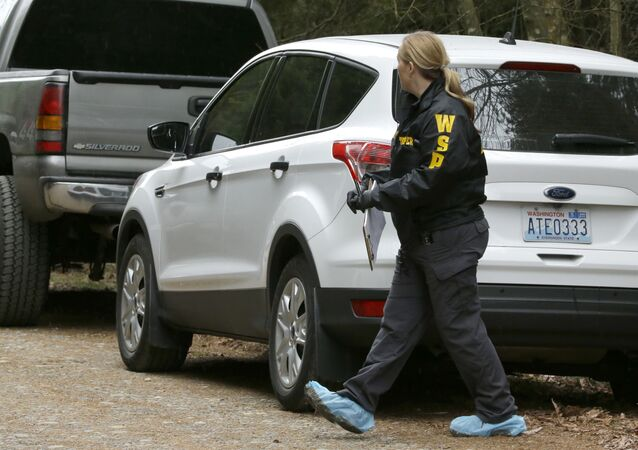 Washington State Patrol detective walks with protective foot covers on near the scene of a fatal shooting Friday, Feb. 26, 2016, near Belfair, Wash