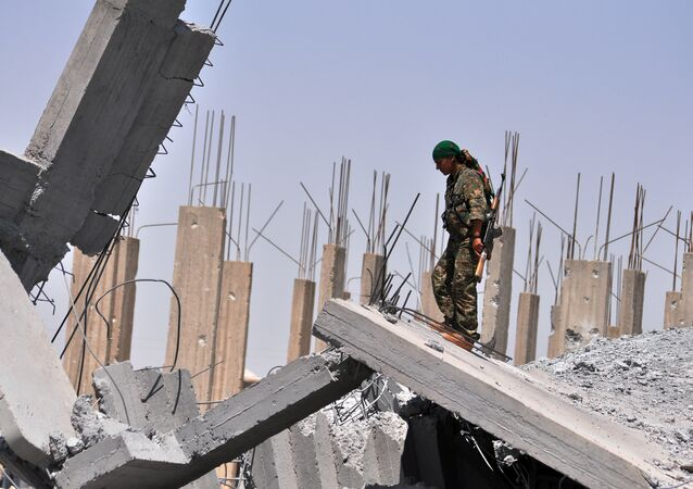 A female fighter from the Kurdish People Protection Unit (YPG) looks at destruction in the Syrian town of Ain Issi, some 50 kilometres north of Raqqa (File)