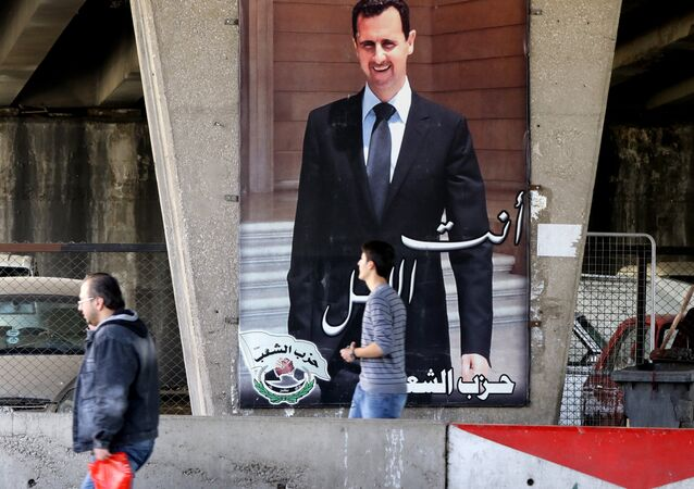 Syrian men walk past a poster bearing a portrait of President Bashar al-Assad in the capital Damascus, on February 27, 2016, as the first major ceasefire of the five-year war takes hold and an international task force prepares to begin monitoring the landmark truce
