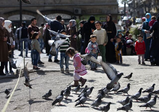 A Syrian girl chases pigeons in Marjeh Square, in Damascus, Syria, Saturday, Feb. 27, 2016