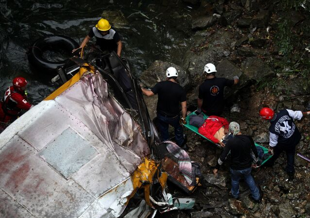 File photo of a rescue workers remove a body from a passenger bus that fell off the road into a ravine in Atoyac, Veracruz state, Mexico, Sunday, Jan. 10, 2016
