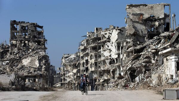 A Syrian boy rides a bicycle through a devastated part of the old city of Homs, Syria, Friday, Feb. 26, 2016 - Sputnik International