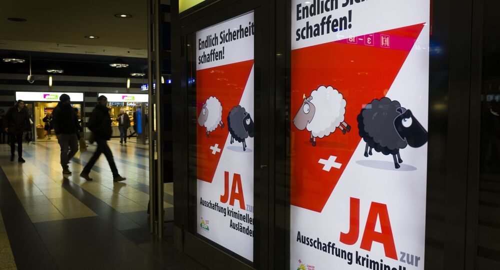 People walk past backlit posters of the right-wing populist Swiss People's Party (SVP) that translate from German as Finally Create Security to advertise their initiative for the eviction of criminal foreigners in Zurich on February 25, 2016