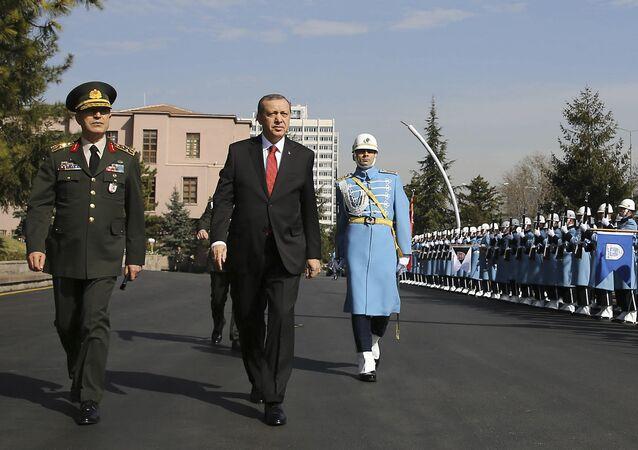 Turkish President Recep Tayyip Erdogan, centre, accompanied by Turkish Forces' Chief of Staff Gen. Hulusi Akar, left, reviews a honour guard Thursday Feb. 18, 2016