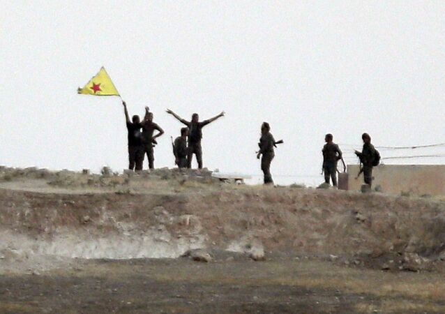 In this Monday, June 15, 2015 file photo taken from the Turkish side of the border between Turkey and Syria, in Akcakale, southeastern Turkey, Kurdish fighters with the Kurdish People's Protection Units, or YPG, wave their yellow triangular flag in the outskirts of Tal Abyad, Syria