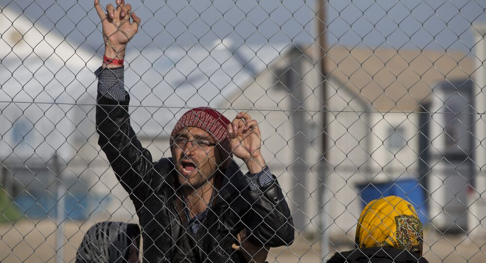 Afghan migrant shouts Merkel help us in the northern Greek border station of Idomeni , Tuesday, Feb. 23, 2016