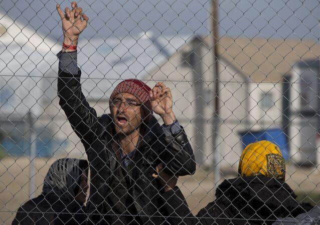 Afghan migrant shouts Merkel help us in the northern Greek border station of Idomeni , Tuesday, Feb. 23, 2016