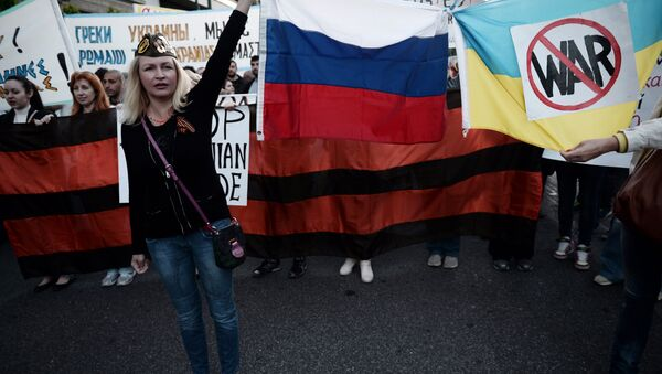 People hold Russian and Ukrainian flags tied together bearing an anti-war symbol (File) - Sputnik International