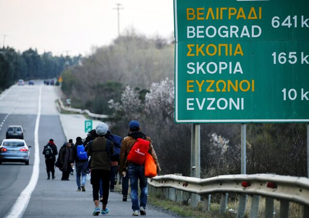 Stranded refugees walk through a national motorway towards the Greek-Macedonian border near the Greek town of Polykastro after ignoring warnings from Greek authorities that the border is shut, as hundreds of migrants set off on the country's main north-south motorway to Idomeni border crossing February 25, 2016.