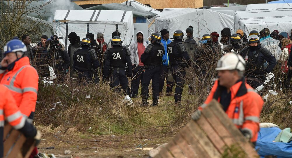 Agents dismantle a shelter as anti-riot policemen stand nearby on February 29, 2016 in the jungle migrants and refugees camp in Calais, northern France