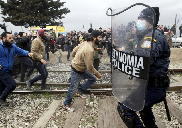 Stranded refugees and migrants try to break a Greek police cordon in order to approach the border fence at the Greek-Macedonian border, near the Greek village of Idomeni, February 29, 2016.