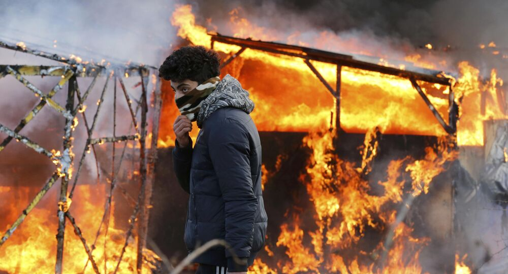 A migrant walks past a burning makeshift shelter set ablaze in protest against the partial dismantlement of the camp for migrants.