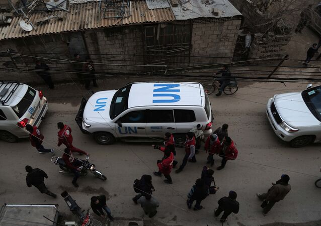 UN vehicles escorting a Red Crescent convoy carrying humanitarian aid arrive in Kafr Batna, in the rebel-held Eastern Ghouta area, on the outskirts of the capital Damascus on February 23, 2016 during an operation in cooperation with the UN to deliver aid to thousands of besieged Syrians.