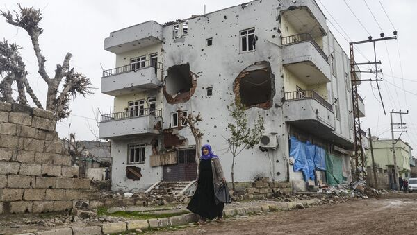 A woman walks past the ruins of a building as curfew ends during daylight in the town of Silopi. (File) - Sputnik International