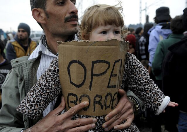 A stranded refugee holds a child during a protest at the Greek-Macedonian border as they wait for the border crossing to reopen near the Greek village of Idomeni, February 28, 2016.