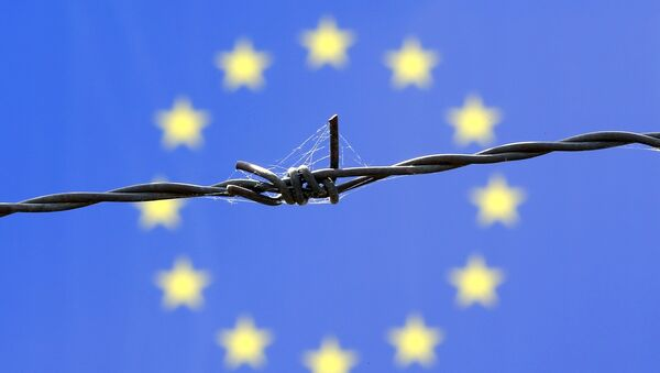 A barbed wire is seen in front of European Union flag - Sputnik International