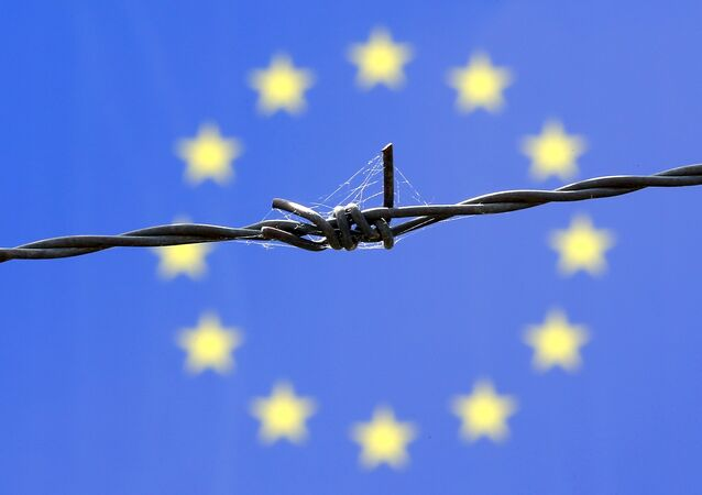 A barbed wire is seen in front of European Union flag
